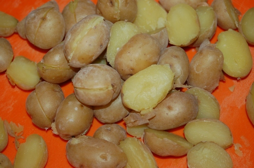 Boil baby potatoes and slice in half.
