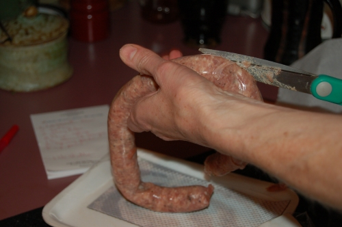 Remove sausage casing by cutting the entire lenght of the sausge adn sliding it off. then it is easy to cut or break the sasge into your pan