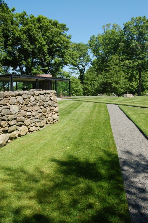 angled paths and a massive stone wall on the walk to The Glass House
